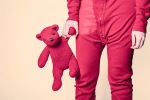 Adulte en pyjamas rouge, un ours en peluche à la main